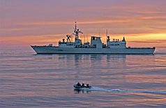 HMCS MONTREAL sails in the sunrise off the Atlantic seaboard on 20 November 2005. A zodiac, with members of HMCS FREDERICTON, head for HMCS WINDSOR, a VICTORIA Class submarine to exchange passengers during Canadian Fleet Operations. Photo:Sgt Roxanne Clowe