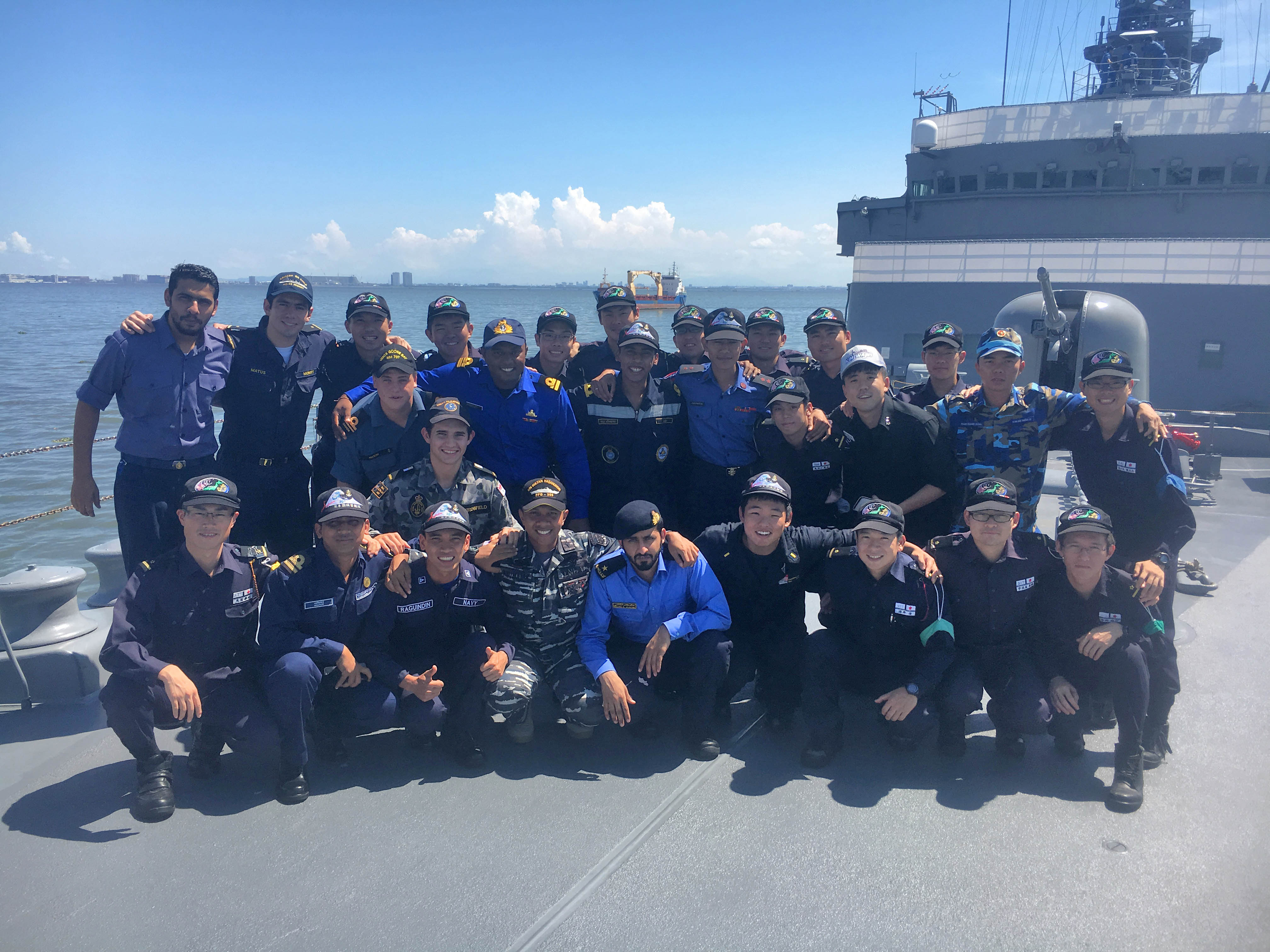Junior officers representing allied international navies pose for a group photo on the deck of Japanese Ship (JS) Kashima during Op REGULUS. SLt Ben Mason from HMCS Scotian is located at the far left side of the middle rows.