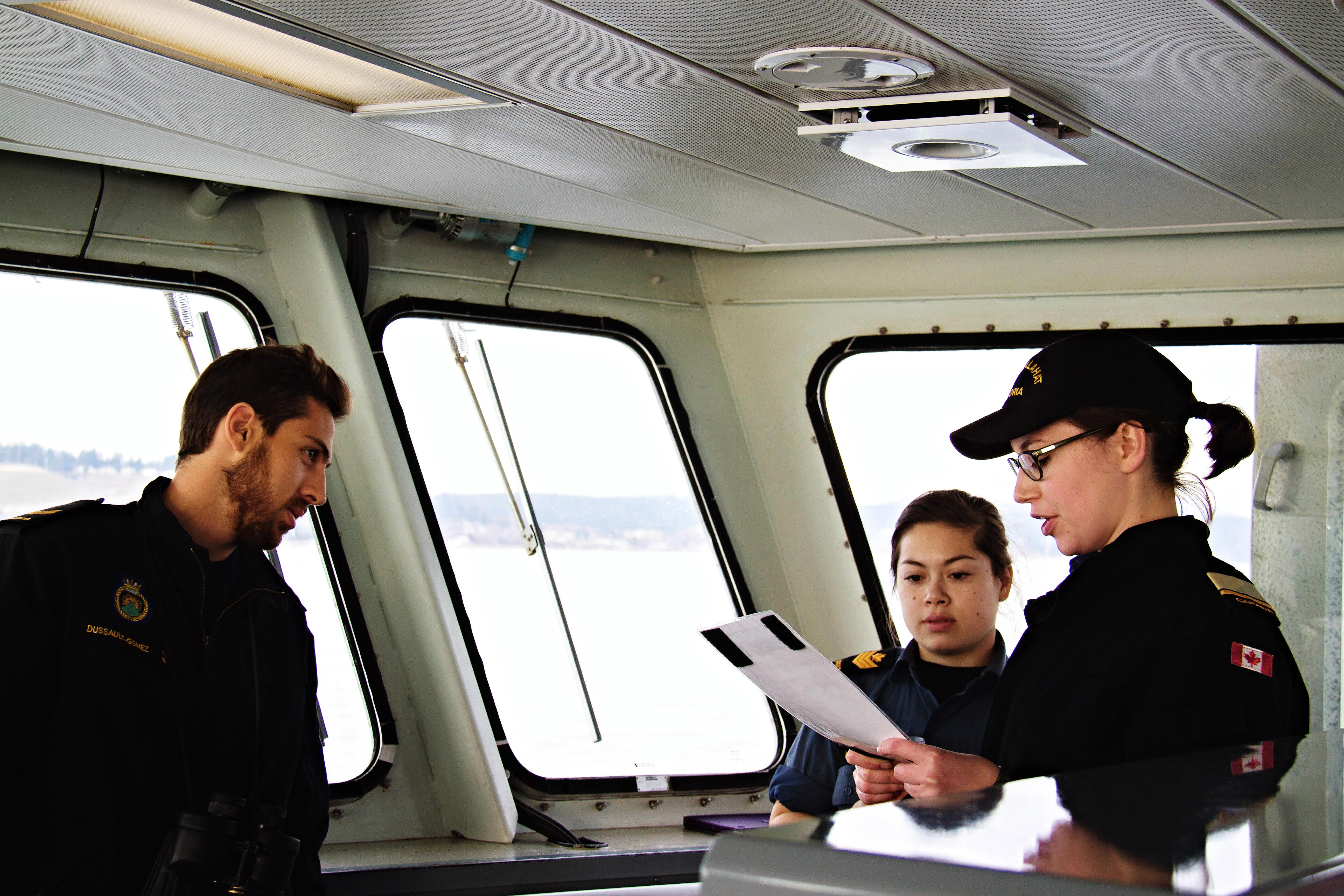 NCdt Elizabeth Mifsud-Sweeney (right) practices a lookout report while Petty Officer 2nd Class Colleen McInnis (center) and Leading Seaman Manuel Dussault-Gomez (left) provide instruction and guidance.