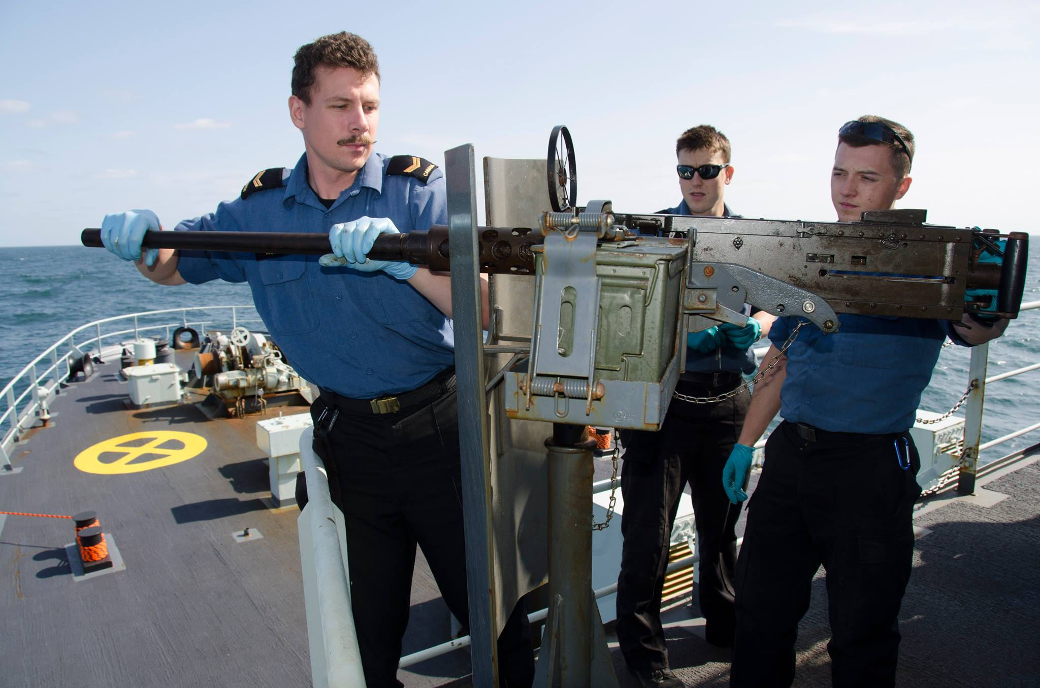LS Laurent Morin along with two other Boatswains maintain HMCS Summerside's .50 Cal Machine-Gun while on Operation CARIBBE