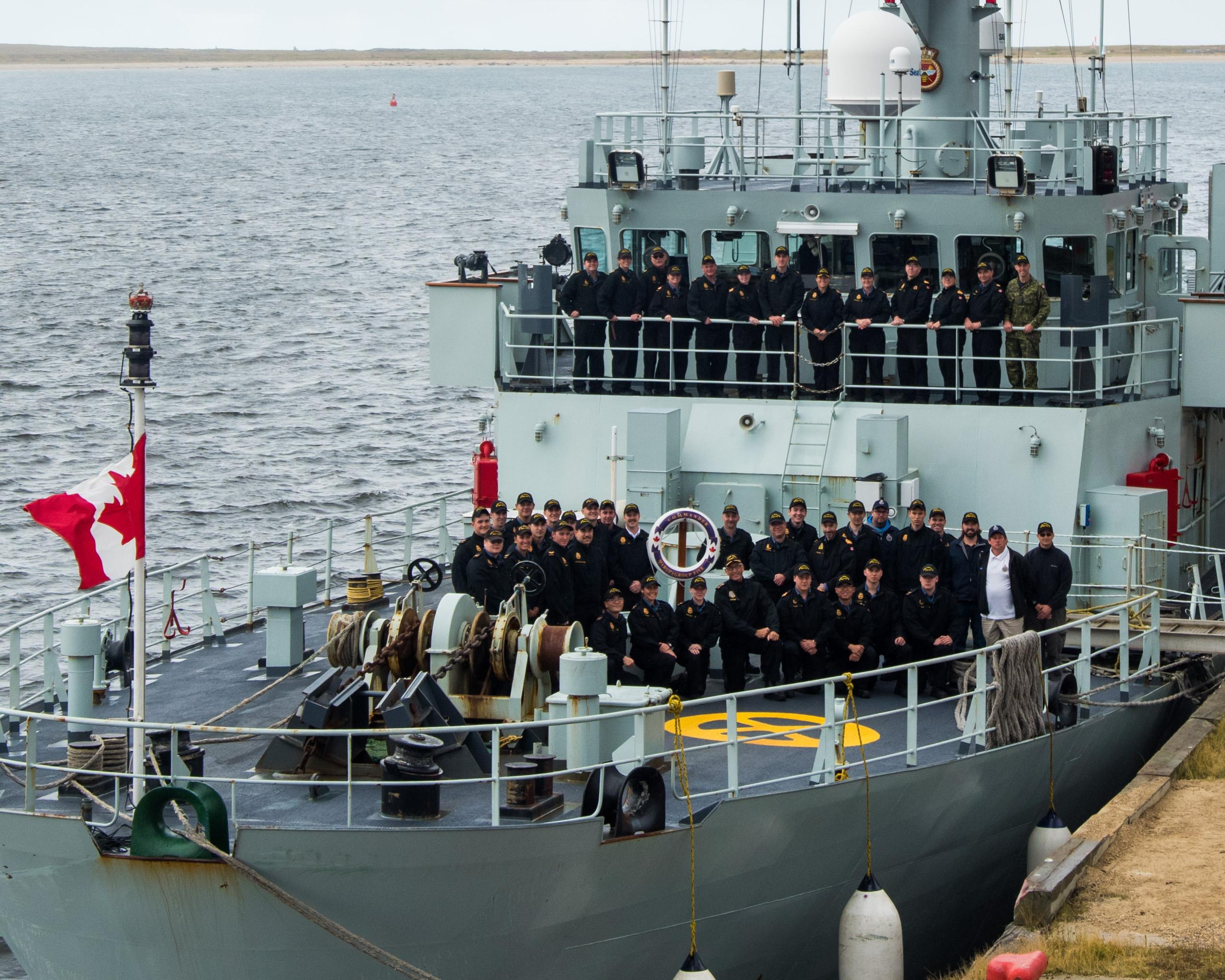 RAdm Newton, joins the crew of HMCS Moncton for a picture alongside Churchill, Manitoba with their bullring freshly painted green.