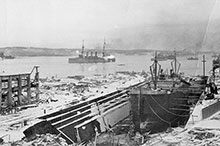 The Halifax Explosion of 6 December 1917 devastated the harbour, but Niobe amazingly survived and can be seen raising steam at the right of this photo.