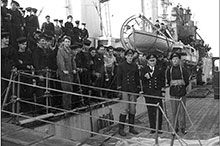 Rear-Admiral L.W. Murray, Flag Officer Newfoundland, greets the crew of the destroyer Assiniboine at St. John's after their sinking of U-210 on 6 August 1942; the ship's captain, Lieutenant- Commander John Stubbs (right), would be lost with his  next ship, Athabaskan.