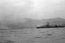 "The Tribal-class destroyer Nootka earning her reputation as a ""train buster,"" bombarding Package 1 on the North Korean ""Windshield"" patrol area, 28 May 1951."