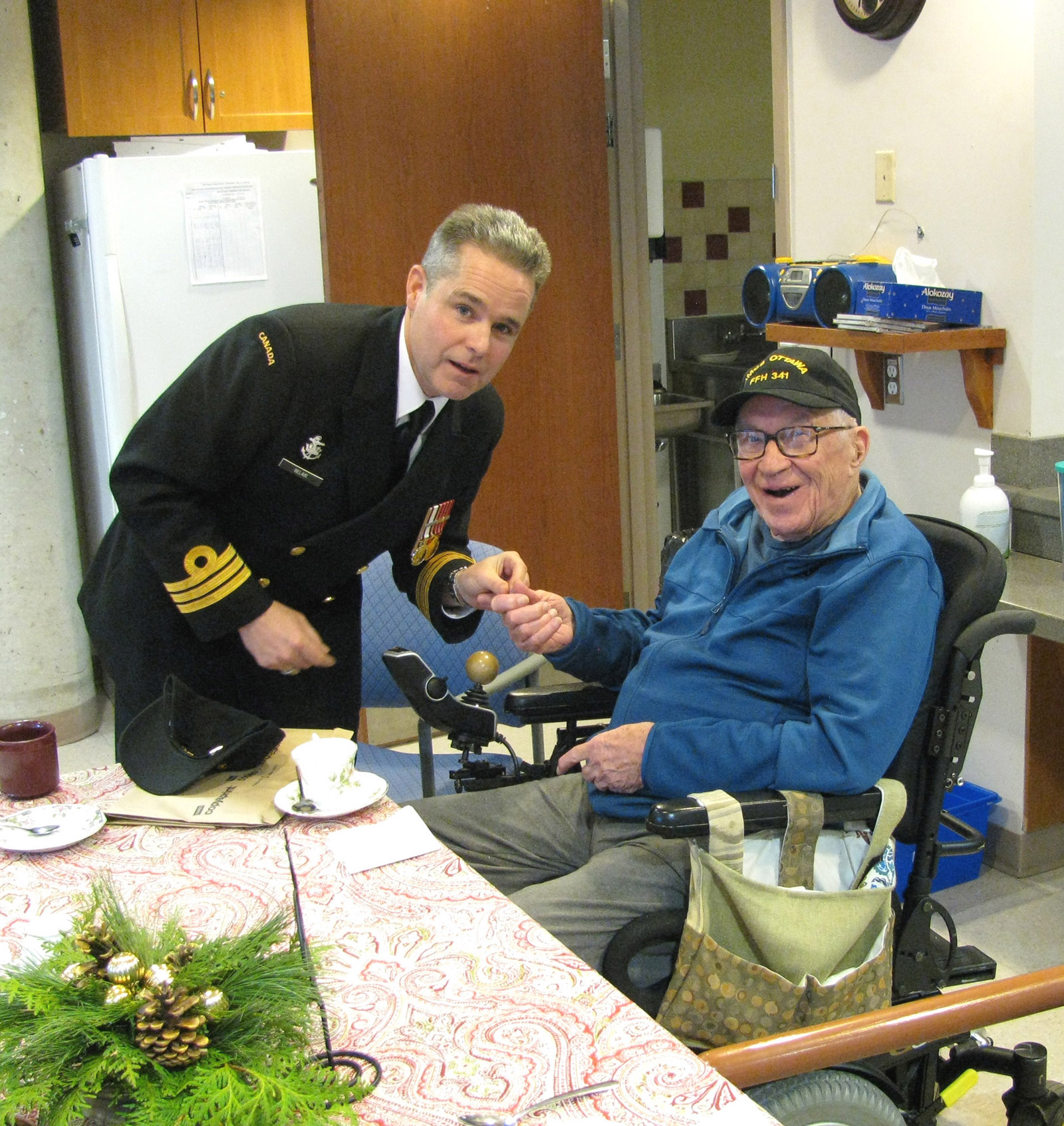 Commander Sylvain Belair, Commanding Officer of HMCS Ottawa, spends time with a resident at the Perley and Rideau Veterans' Health Centre.