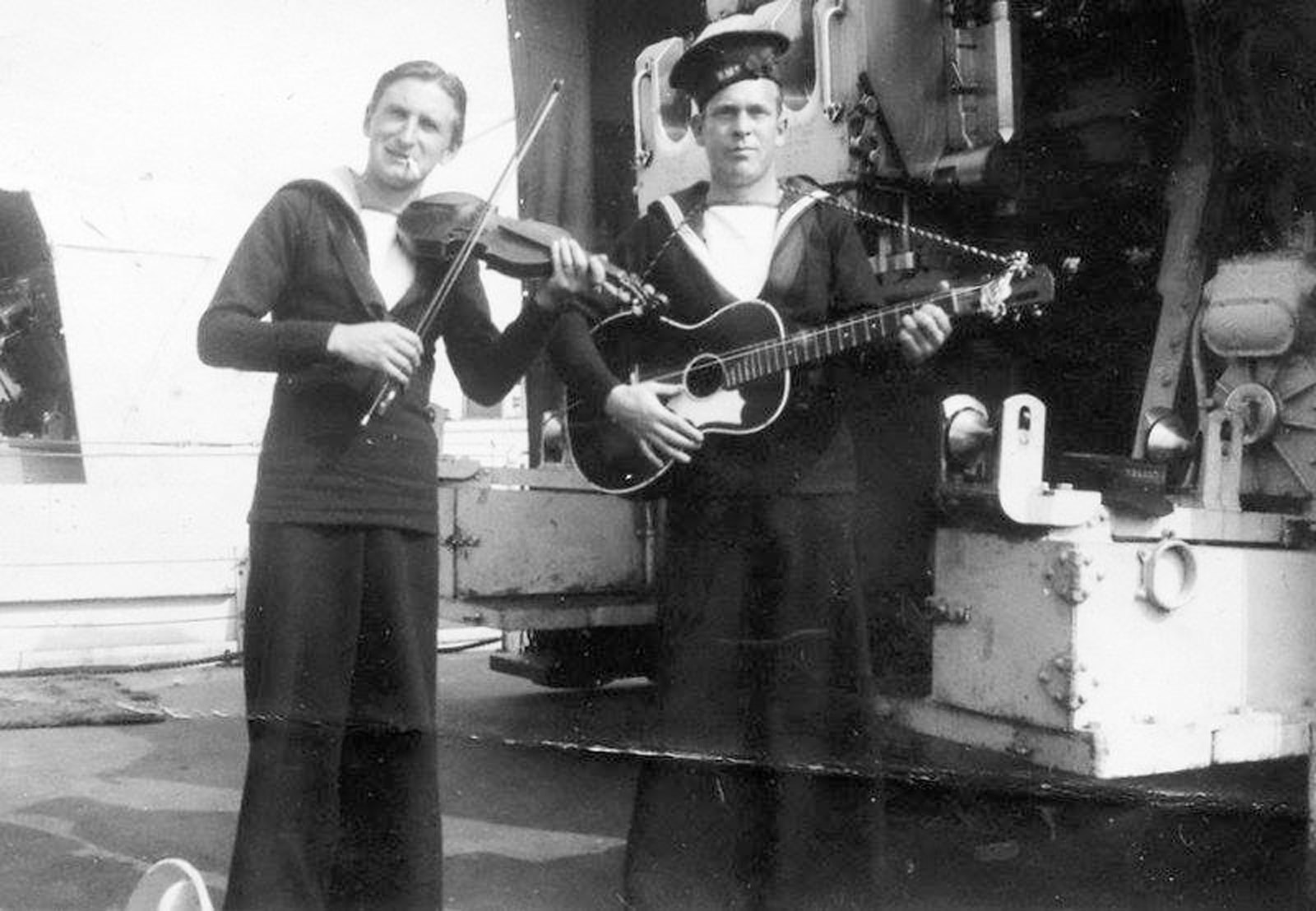 Lieutenant (Navy) Brendan Ryan's grandfather Harvey Mouland, right, plays his guitar while at sea aboard HMS Berkeley.