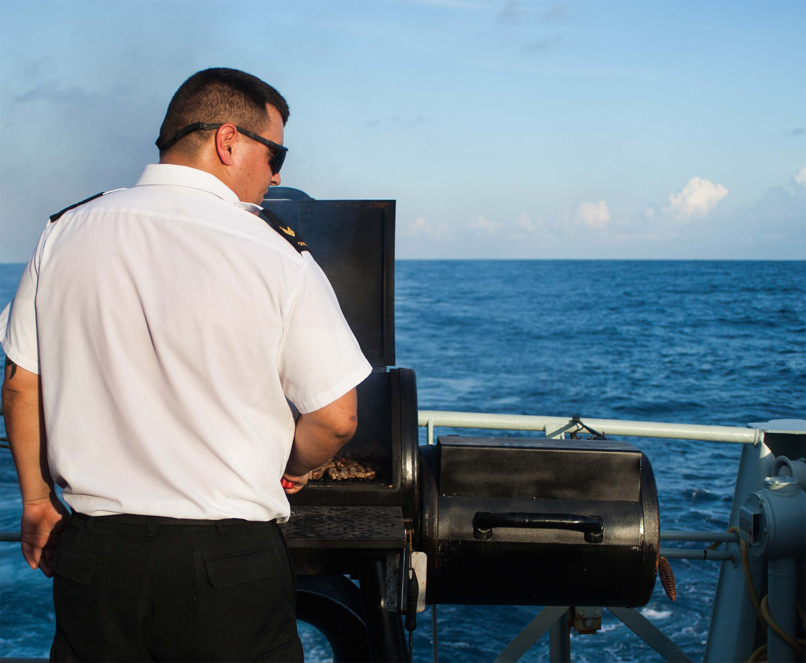 Leading Seaman Zachery Warwick, chief cook aboard HMCS Brandon, prepares a barbecue for the crew.