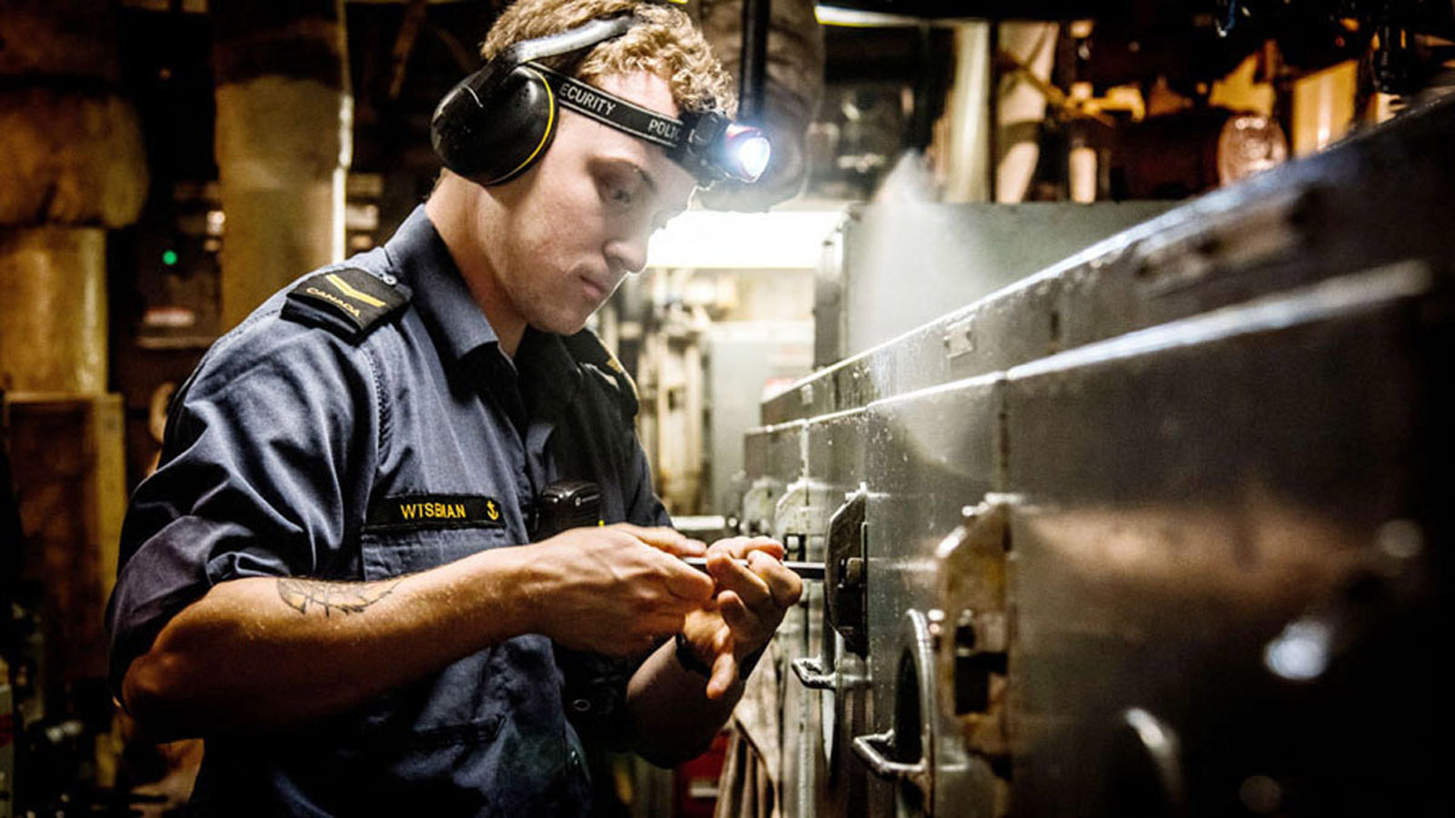 Leading Seaman Jacob Wiseman of HMCS Montréal opens an engine containment to check the oil level.