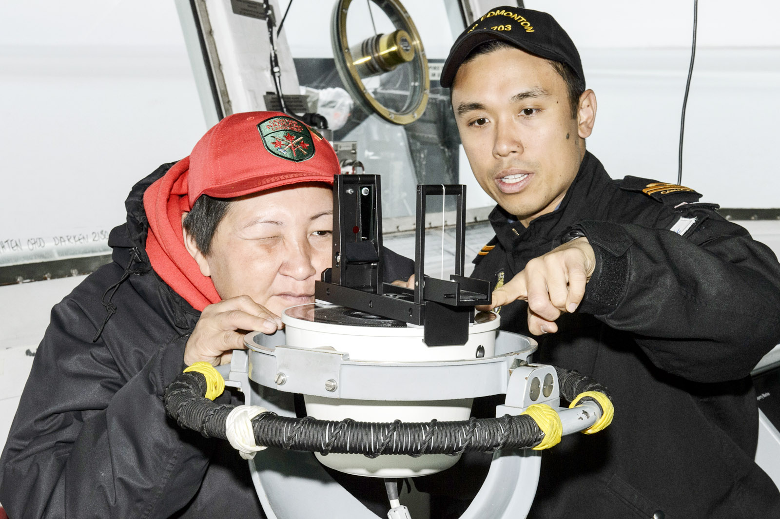 Sub-Lieutenant Andrew Chong of HMCS Edmonton shows Canadian Ranger Donna Ruben from Palatuk, N.W.T., how to take a bearing during a familiarization tour as part of Op Limpid.