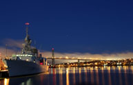 HMCS Fredericton glows in the reflecting lights of Halifax during the early morning hours of January 17.