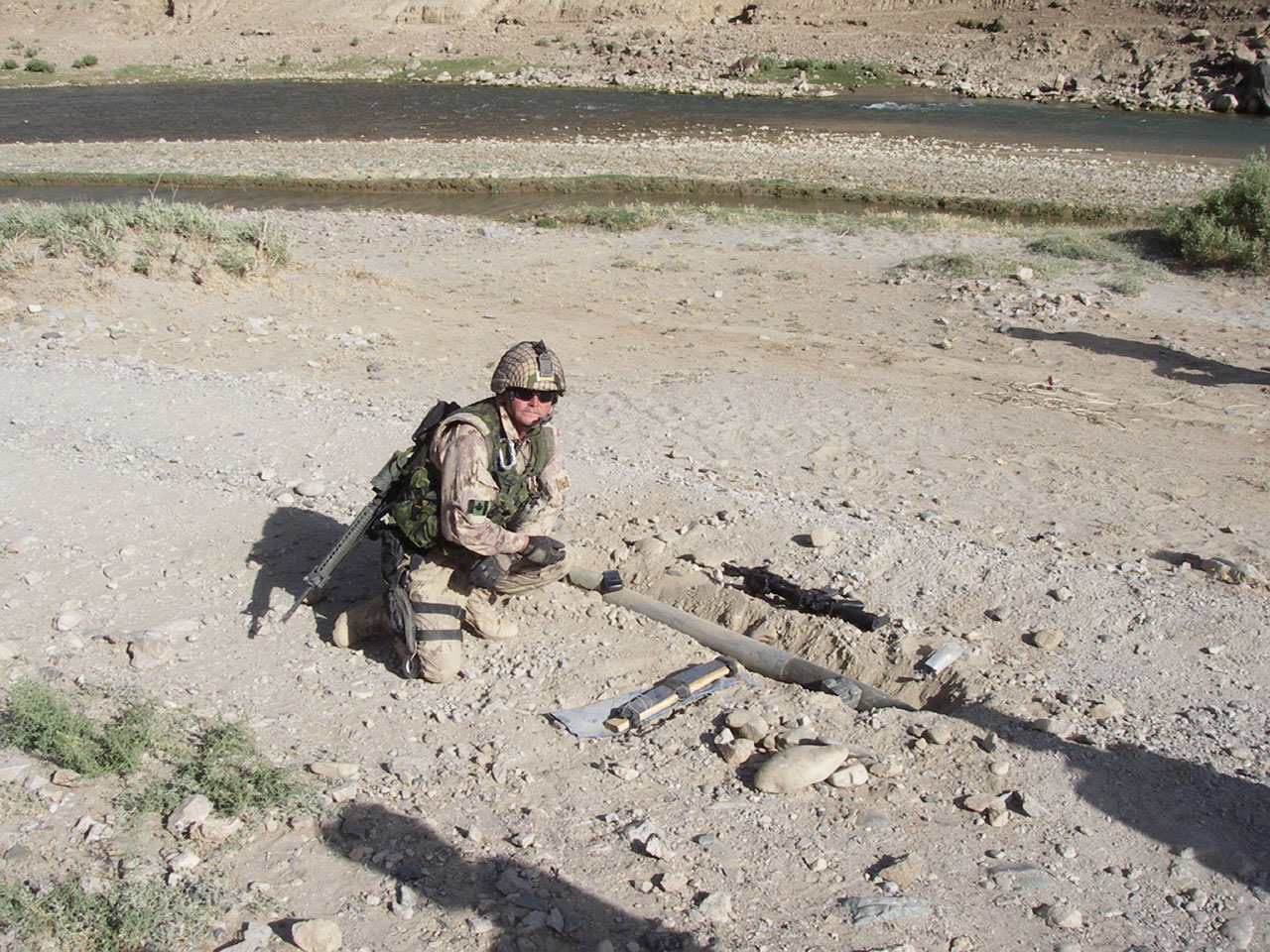 A navy diver displays an IED he has just dismantled and rendered safe.