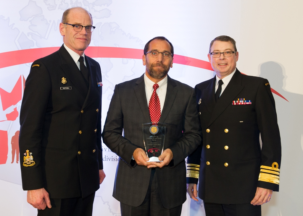 LCdr (Ret'd) Antonia Zezza accepts his award from VAdm Mark Norman, Royal Canadian Navy (RCN) Commander, and CPO1 Tom Riefesel, RCN Command Chief Petty Officer.