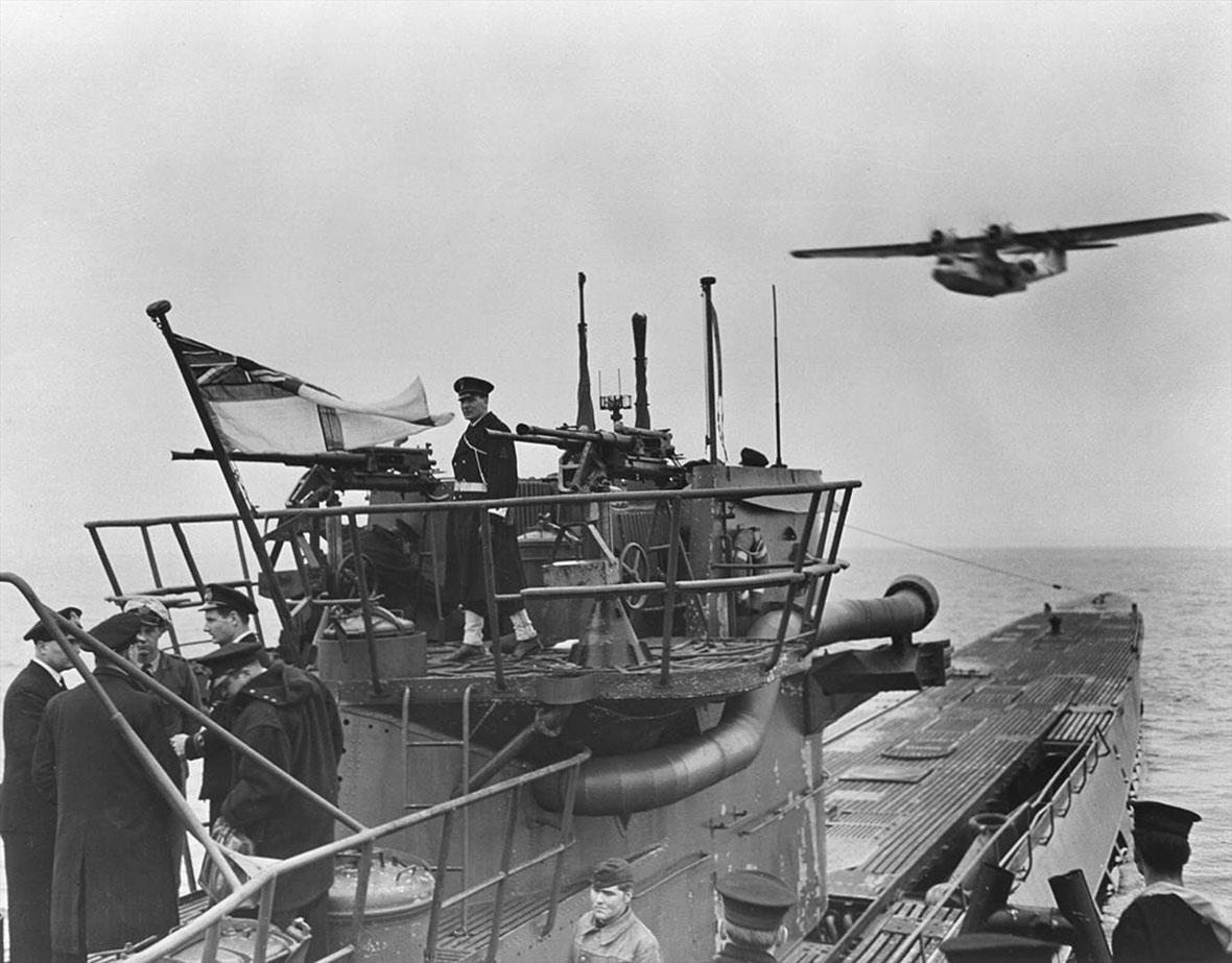 An RCN crew handles the surrendered U-889 off Shelburne, N.S., as a Royal Canadian Air Force Canso flying boat passes overhead.