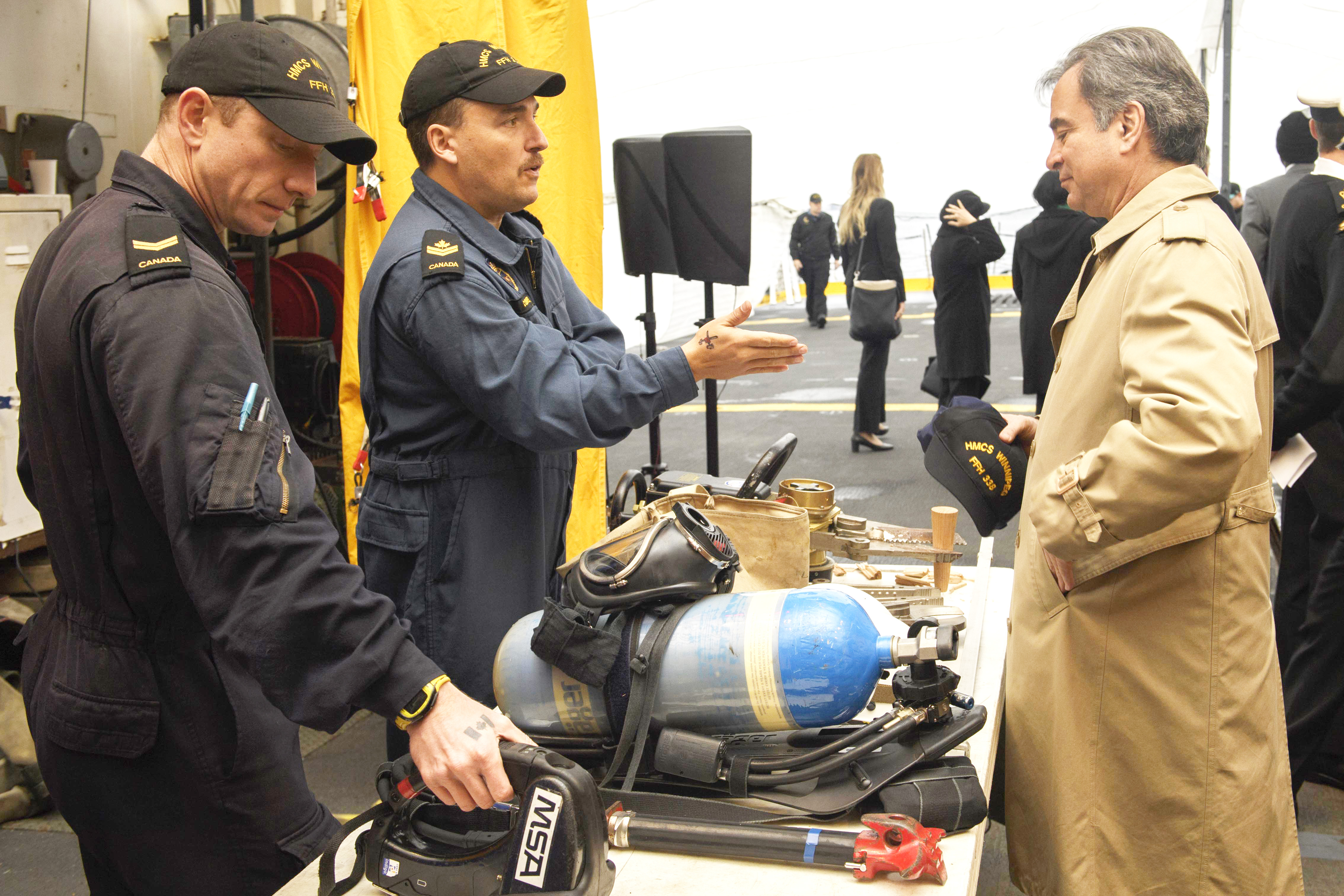 Marine Technicians Leading Seaman Nathan Gillis and Master Seaman Martin Couture describe the firefighting equipment used onboard HMCS Winnipeg to a delegate attending the United Nations Peacekeeping Ministers' Conference during a tour of the ship.