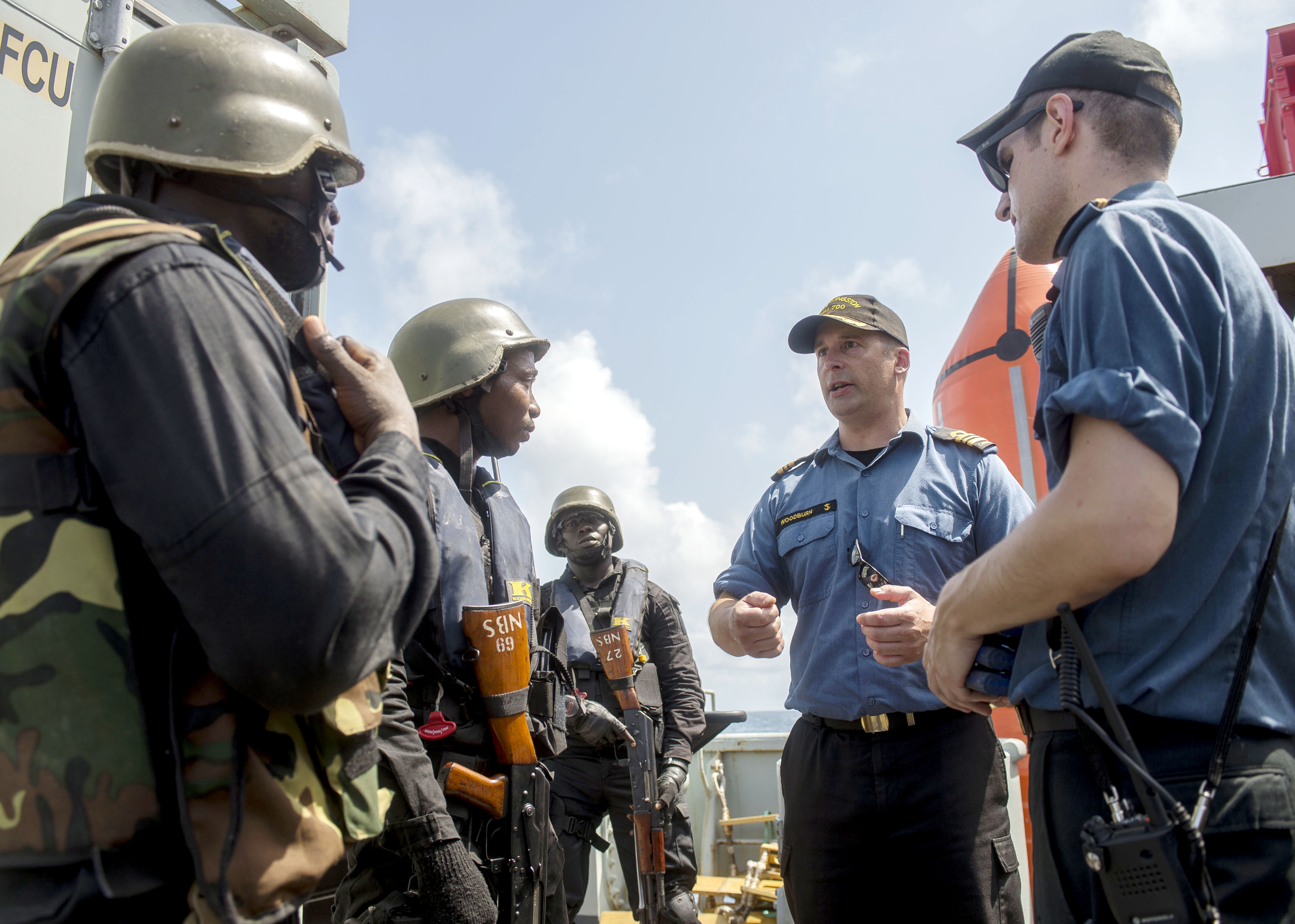 Lieutenant-Commander Matt Woodburn, Commanding Officer of HMCS Kingston and Task Force Commander for Op PROJECTION, talks with a member of the Ghana Navy after a boarding party exercise during OBANGAME EXPRESS.