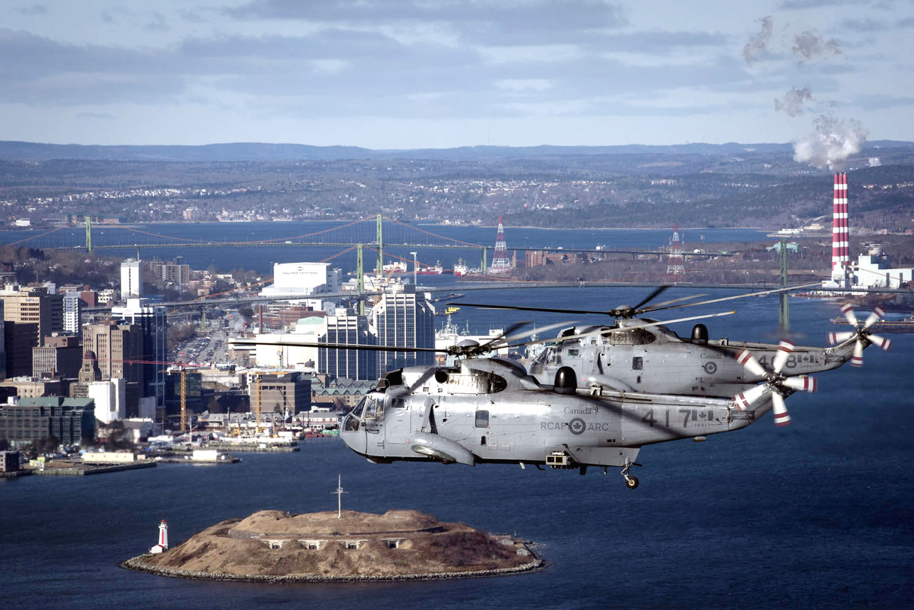 Sea King helicopters from 423 Maritime Helicopter Squadron, fly over Halifax Harbour on January 26, 2018.