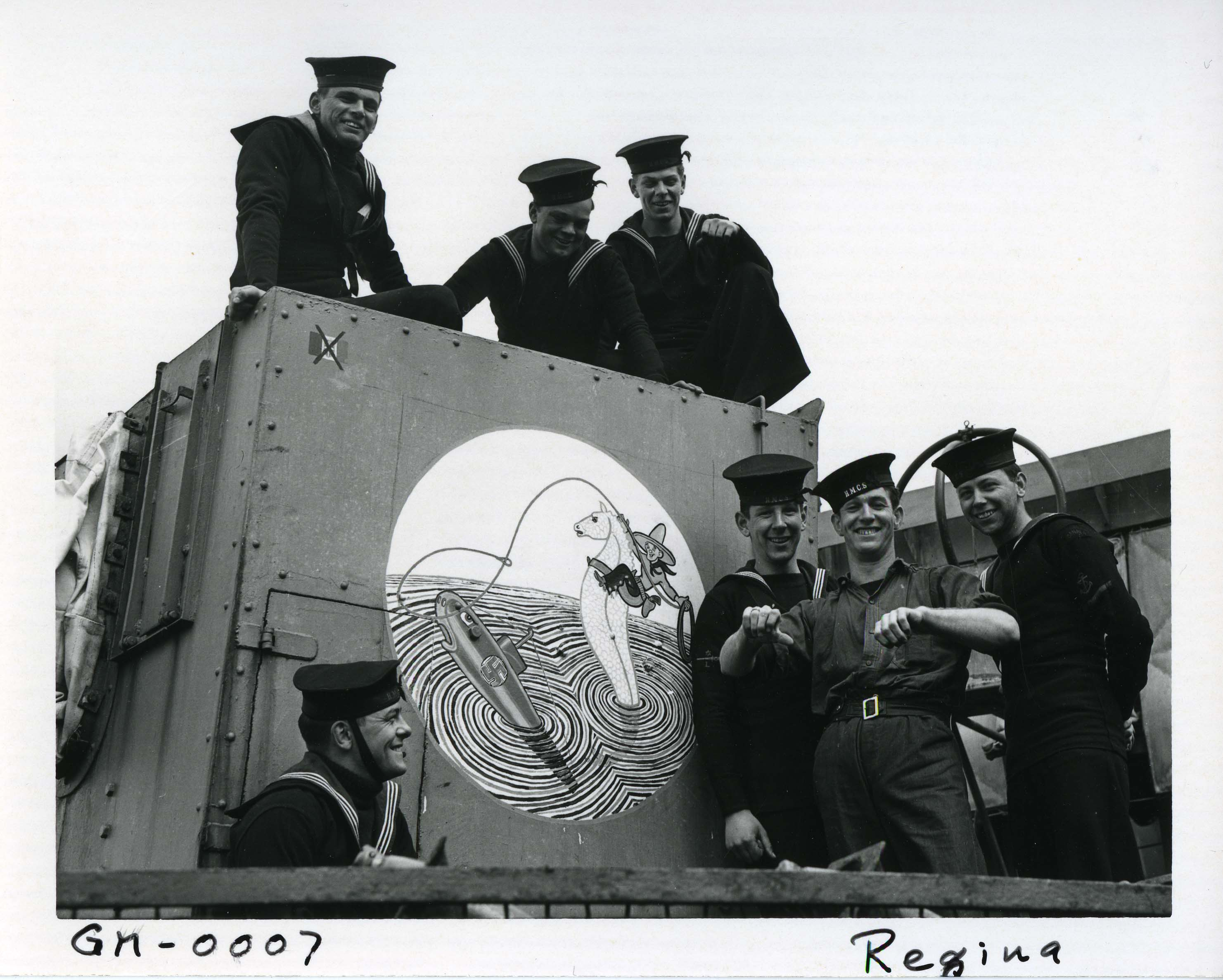 "Crew members from HMCS Regina pose with their ship's gun shield art – a stylized sea ""horse"" wrangling a German U-boat – circa 1943."