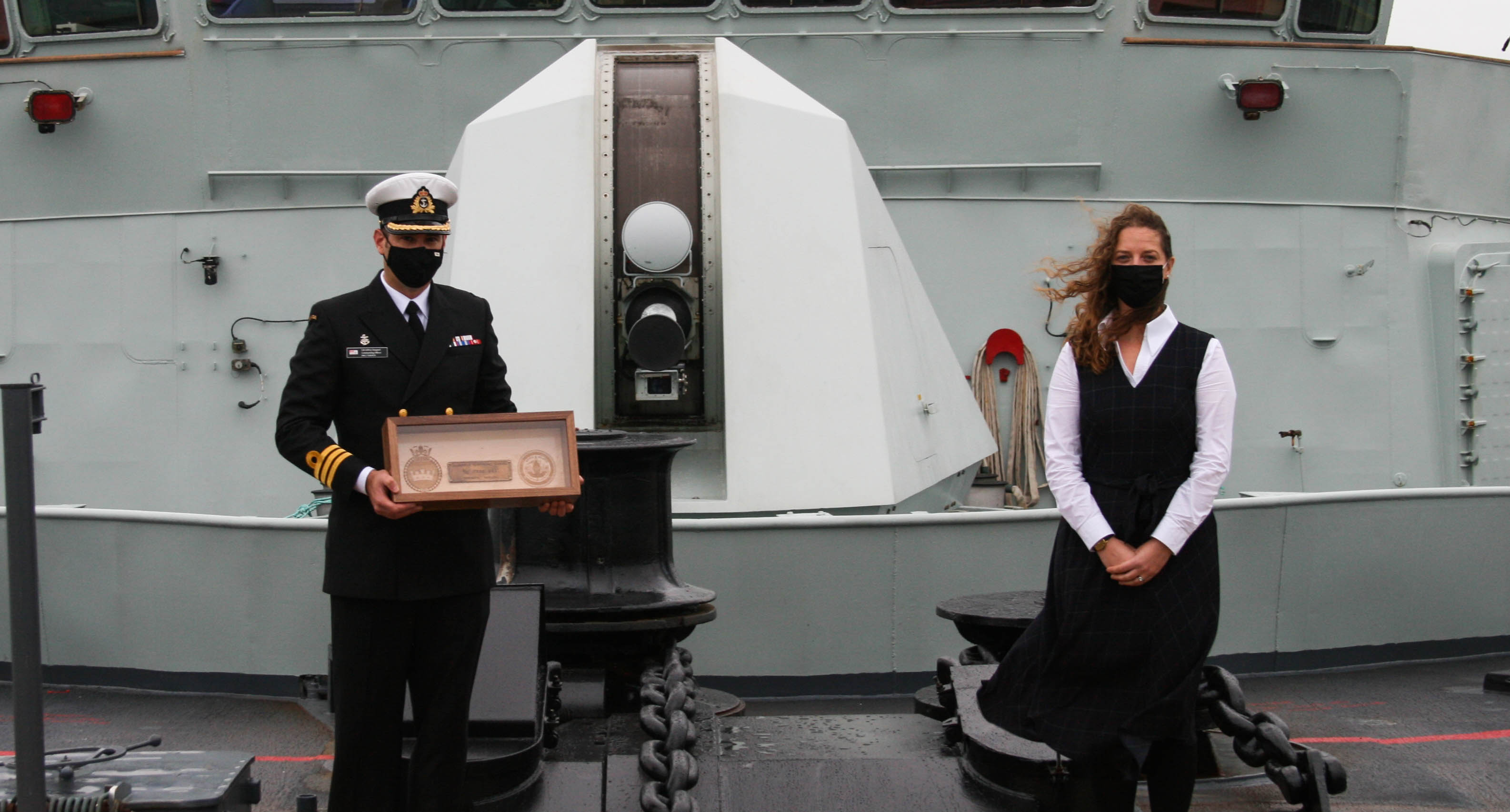 Cdr Jeff Dargavel, left, Commanding Officer of HMCS Toronto, and Camilla Moore, United Kingdom's Receiver of Wreck, on board HMCS Toronto for the presentation of the brass fuse box plate.