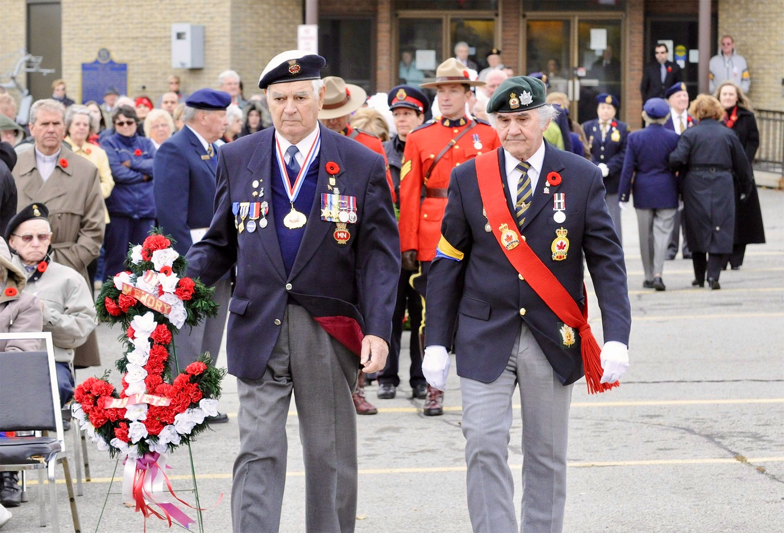 Mr. Wetherall (left) lays a wreath at a modern-era Remembrance Day ceremony.